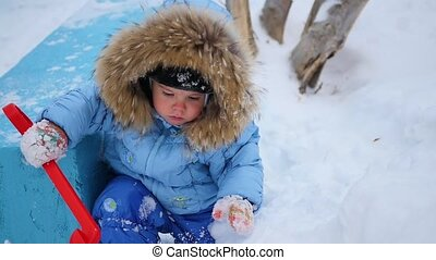 a funny child plays with a toy shovel in the snow