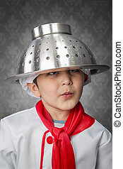 A funny little boy cook in uniform over vintage  background