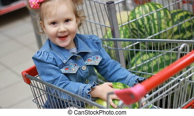 A funny little girl in a grocery store sits in a food cart holding a watermelon in her hands. A child is shopping for a vegetarian meal