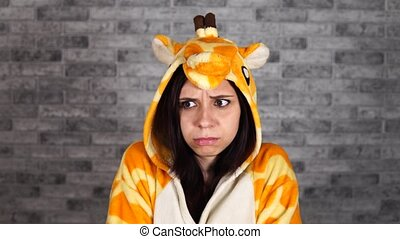 A funny woman in a big pajamas of giraffe is showing a ...