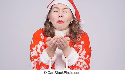 A funny young woman in Santa Claus hat sneezes at confetti