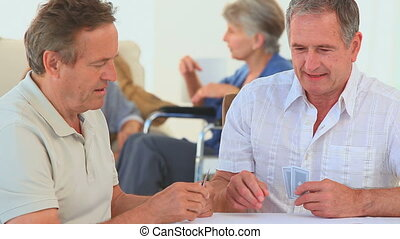 A game of cards between two elderly friends