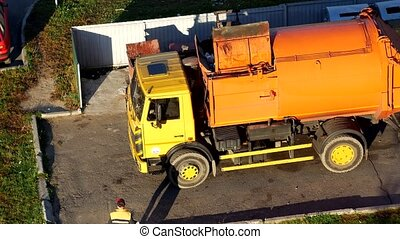 A garbage truck cleans garbage cans in the courtyard of a residential area from garbage and takes it to landfill