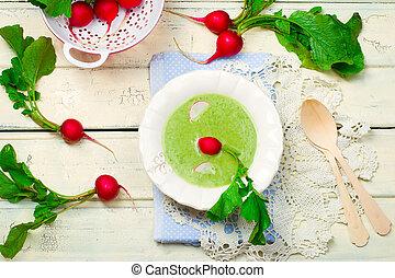 a garden radish cream soup on a white wooden background....
