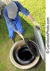 Gardener obove underground rainwater cistern