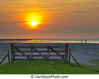 A gate at the wadden sea during sunset