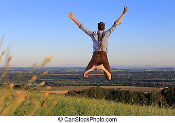 German Man in Bavarian dress jumping happily on lawn