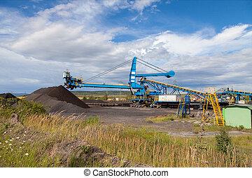 A giant wheel excavator in brown coal mine, cloudy sky.