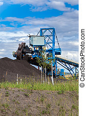 A giant wheel excavator in brown coal mine , cloudy sky.