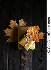 A gift box in golden paper, dry leaves, autumn