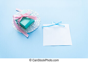 a gift on a white napkin and card on blue background