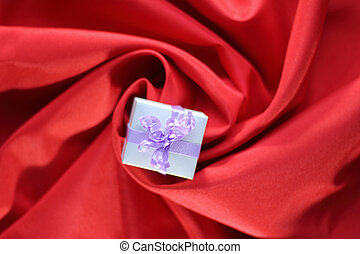 gift with ribbon placed in the center of a spiral of red satin fabric