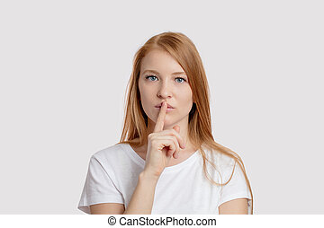 a ginger girl with a finger in front of her lips