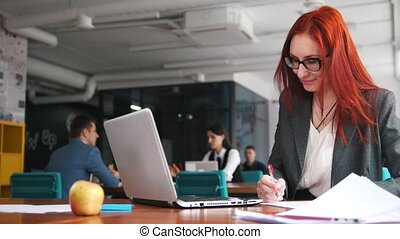 A ginger woman sitting at office and working by the laptop...