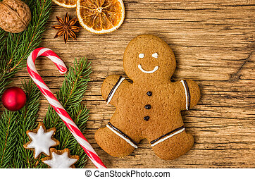 A gingerbread man on a wooden background with christmas decorations