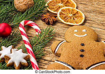 A gingerbread man with a candy cane and christmas decorations