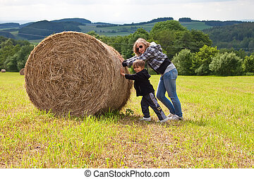 A girl and a boy pushing a round bundle of straw.