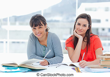 A girl and her friend smiling as they look into the camera while doing homework