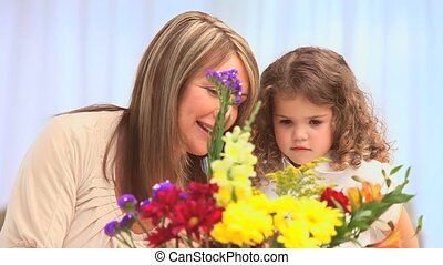 A girl and her grand mother making a bunch of flowers in the...