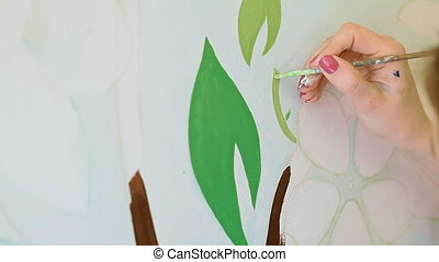 A girl artist is decorating a wall in the apartment
