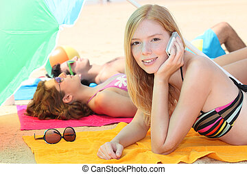 a girl at phone and her friends leaning down on the beach