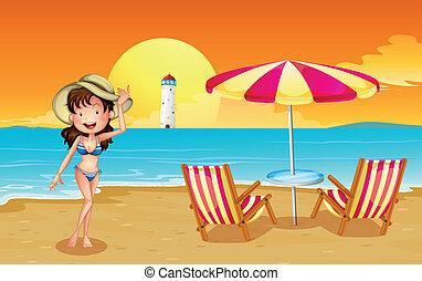 A girl at the beach across the lighthouse