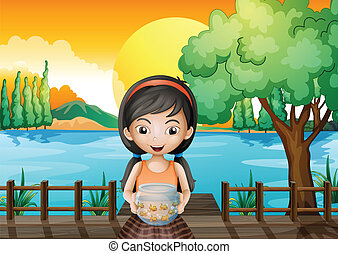 A girl at the bridge holding an aquarium