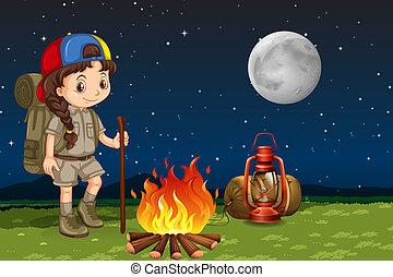 A girl camping at night