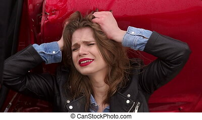 A girl crying sitting on the ground near a broken car, she was in an accident.