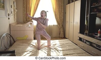 A girl dances boogie vugi at home on a bed in bright light, ...