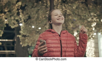 A girl dances in the street listening to a song
