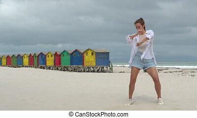 A girl dancing on the white sands of South Africa near the colorful wood Muizenberg Beach Houses.