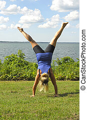 A girl doing a hand stand - An athletic girl does a hand...