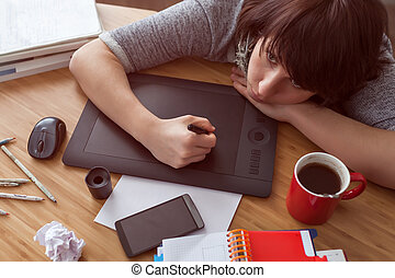 A girl draws a picture on a graphic tablet. She looks tiredly at the monitor. Various items on the table.