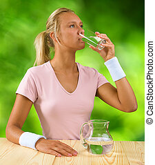 a girl drinking water from glass