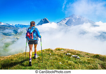 A girl during a hike in the mountains with poles sticks