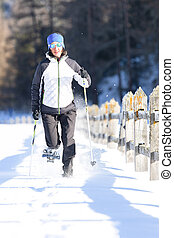 A girl during a ride with snowshoes and poles.