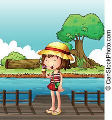 A girl eating an ice cream at the bridge