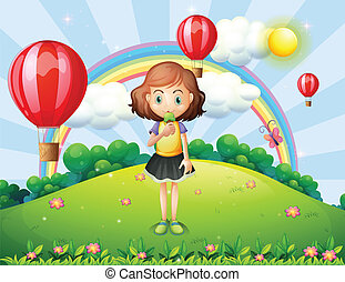A girl eating an ice cream at the hilltop with hot air balloons