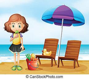 A girl eating an icecream at the beach
