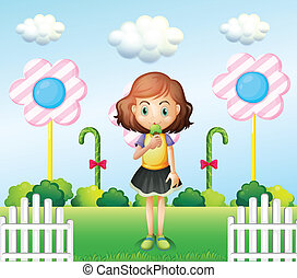 A girl eating an icecream near the fence with giant candies