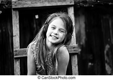 A girl enjoy music with headphones in the country outdoors. Black and white photo.