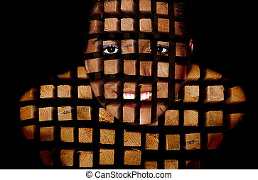 A girl from the wooden bars on a black background
