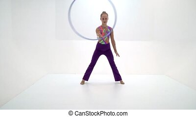 A girl gymnast performs an exercise with a hoop. The concept...
