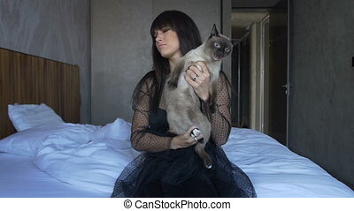 A girl holding a cat on his hands as he tries to escape