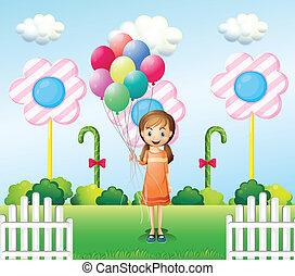 A girl holding balloons in the garden