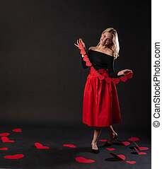 A girl holds a garland of Valentine's heart symbol, Valentine's heart, on the floor hearts of romance . the honeymoon formula. the feeling of joy in the red dress girl, barefoot