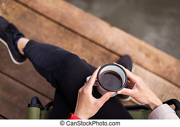 A girl holds a metal cup of coffee in her hands near the lake while sitting on a wooden pier. Close-up, top view.
