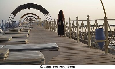 A girl in a bathing suit and a cloak is walking along the pier at dawn
