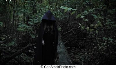 A girl in a black cloak with a hood shows her finger...